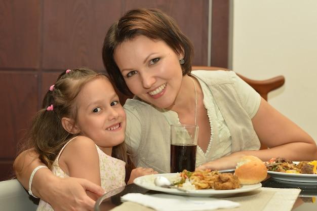 Mère et fille mangeant à table à la maison