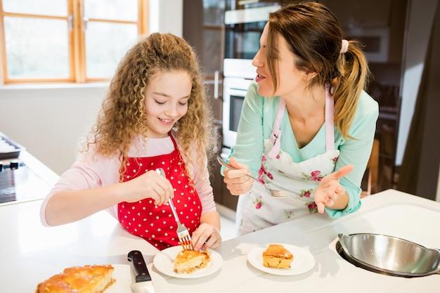 Mère et fille de manger crêpes dans la cuisine
