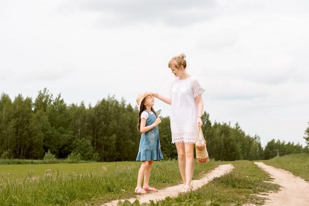 Mère et fille marchant dans la forêt et se tenant la main.