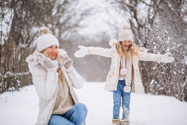 Mère avec fille marchant ensemble dans un parc d'hiver