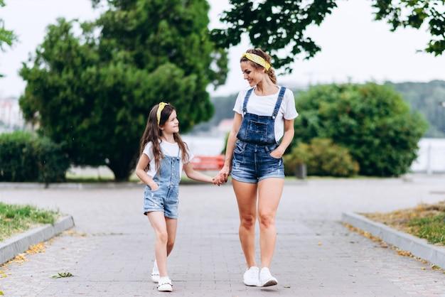 Mère et fille marchant main dans la main et se regardant en plein air.