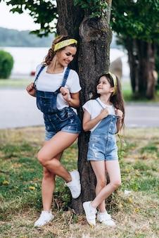Mère et fille marchant en se penchant sur l'arbre et se regardant en plein air.