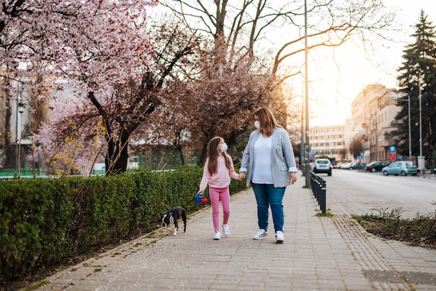 Mère et fille avec des masques de protection sur le visage profitant d'une promenade dans le parc avec leur chien.