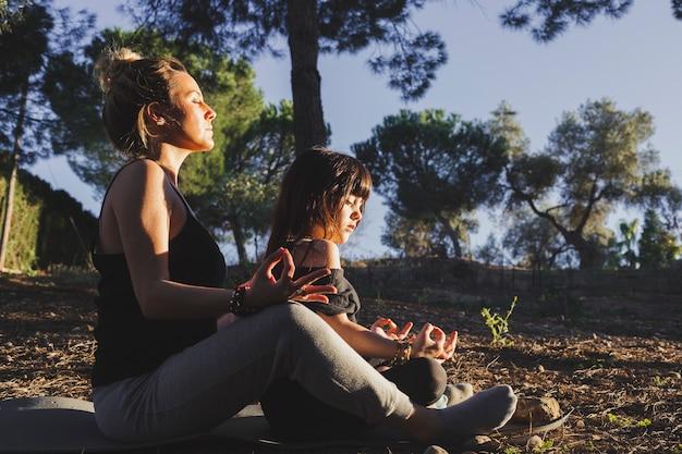 Mère et fille méditant dans le parc