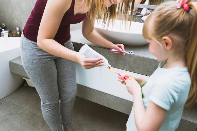 Mère et fille mettant du dentifrice sur les pinceaux
