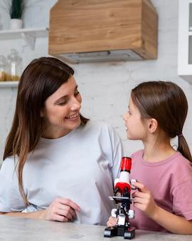 Mère et fille avec microscope faisant des expériences scientifiques