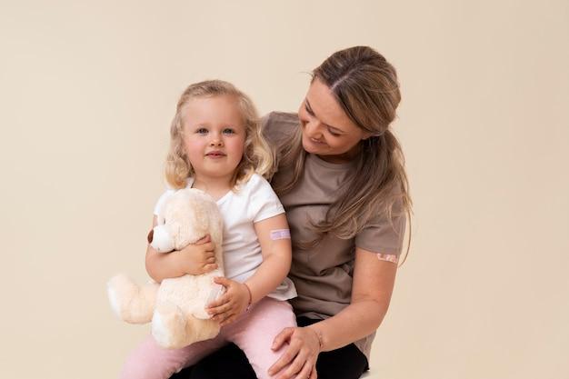 Mère et fille montrant un autocollant sur le bras après avoir reçu un vaccin