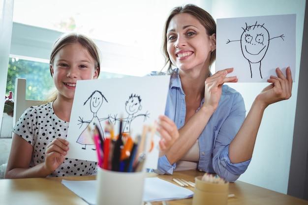 Mère et fille montrant leurs dessins
