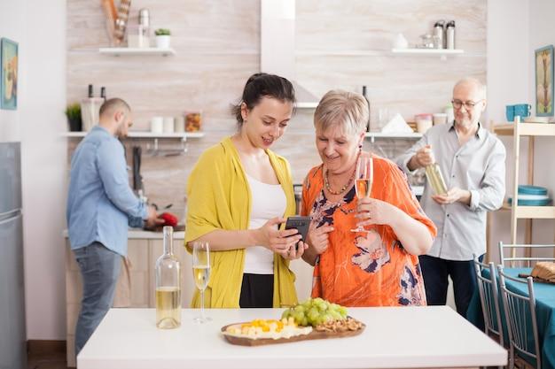 Mère et fille naviguant sur smartphone dans la cuisine pendant le brunch familial. senior woman holding verre de vin blanc. apéritif savoureux.