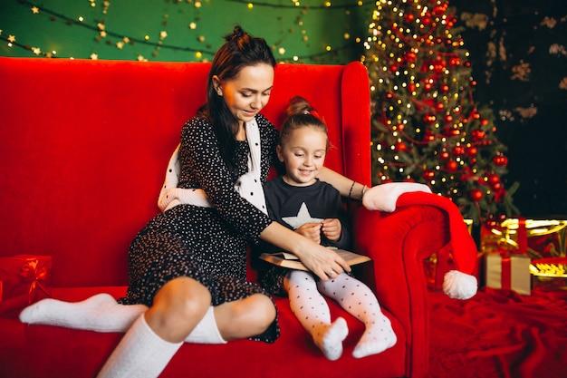Mère avec fille à noël assis sur un canapé avec des cadeaux