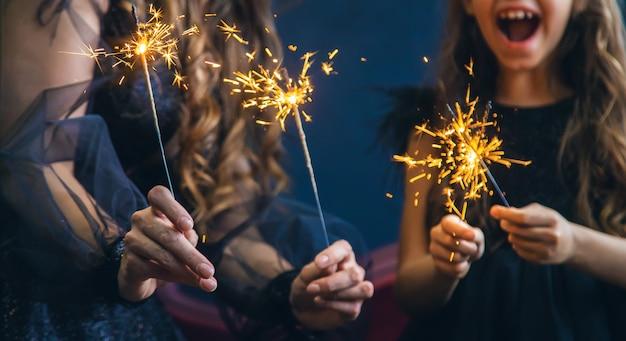Mère et fille ont allumé des feux de bengale dans la nuit de noël.