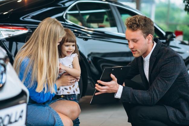 Mère avec fille parlant à un vendeur dans une salle d'exposition