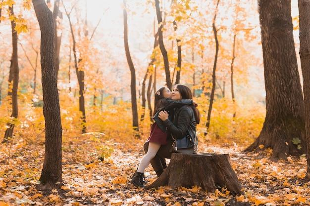 La mère et la fille passent du temps ensemble pendant la saison des parcs jaunes d'automne et le concept de parent seul
