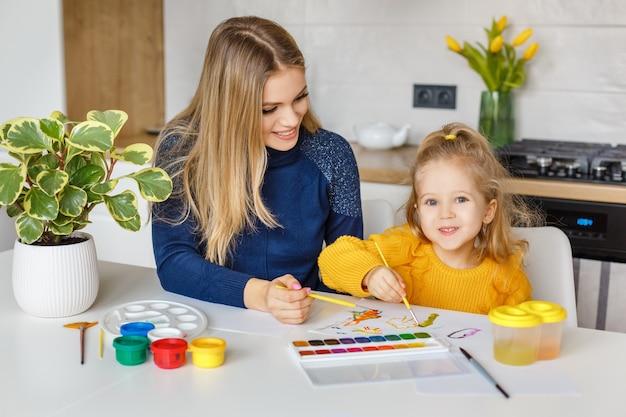 Mère et fille peignant à la maison. kid s'amusant. éducation de la petite enfance, loisirs préscolaires