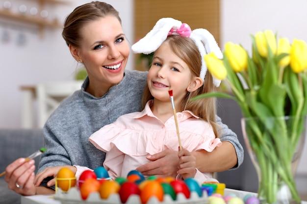 Mère et fille peignant des œufs de pâques à la maison