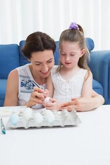 Mère et fille peignant des oeufs de pâques