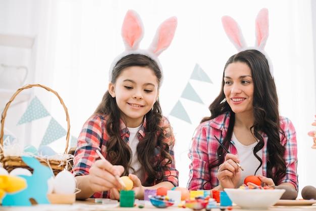 Mère et fille peindre les oeufs de pâques avec une brosse