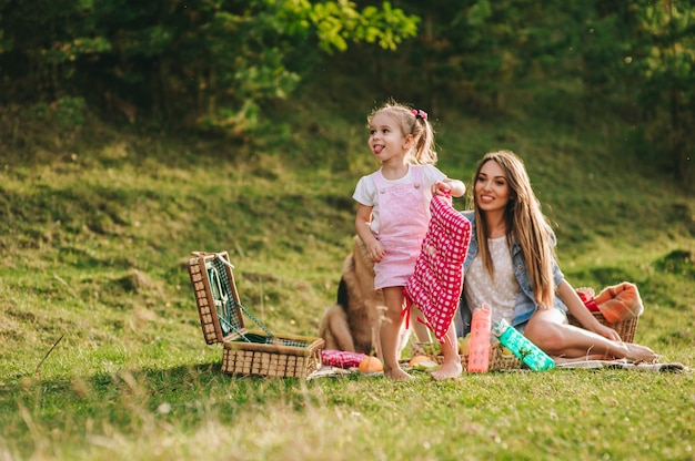 Mère et fille à un pique-nique avec un chien