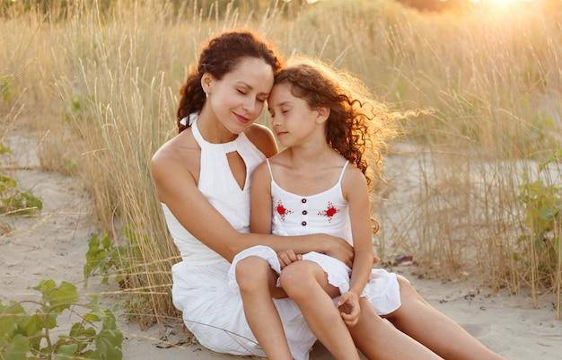 Mère et fille sur la plage au coucher du soleil