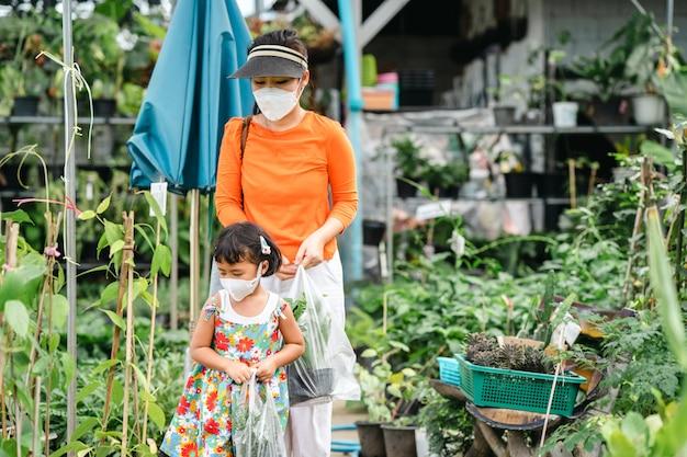 Mère et fille portant un masque protecteur marchant dans un magasin d'arbres