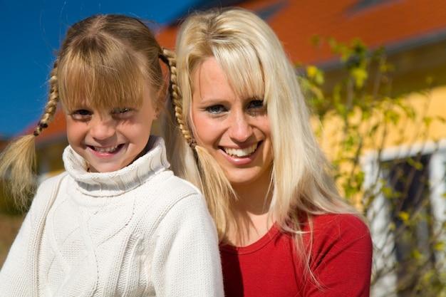 Mère et fille posant devant une maison