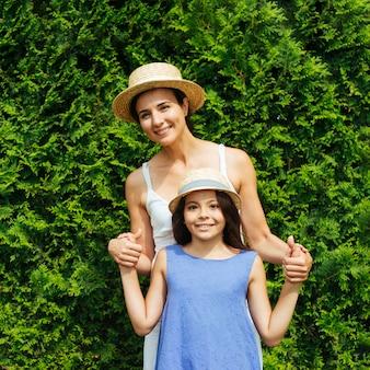 Mère, fille, poser, devant, buissons