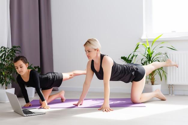 Mère et fille pratiquant un cours de yoga en ligne à la maison pendant la période d'isolement en quarantaine pendant la pandémie de coronavirus. famille faisant du sport ensemble en ligne depuis la maison. mode de vie sain