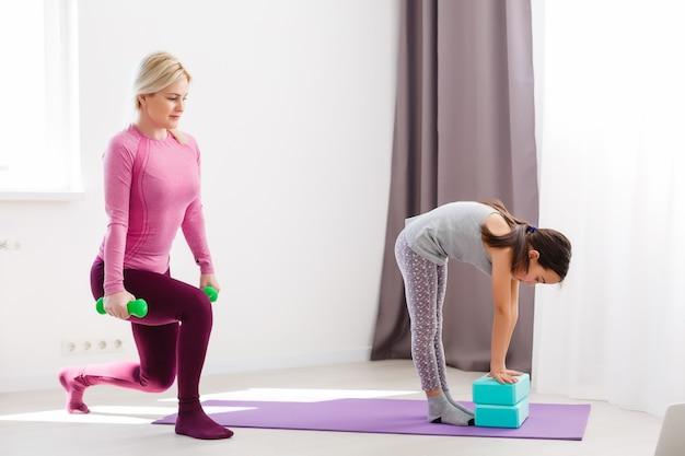Mère et fille pratiquant le yoga à la maison