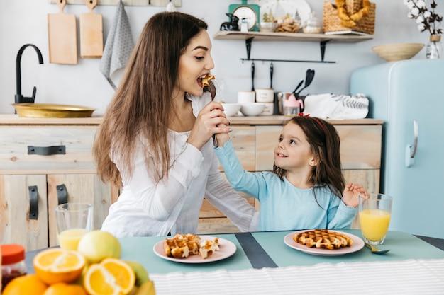 Mère et fille prenant son petit déjeuner