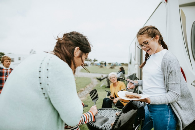 Mère et fille préparant de la viande grillée