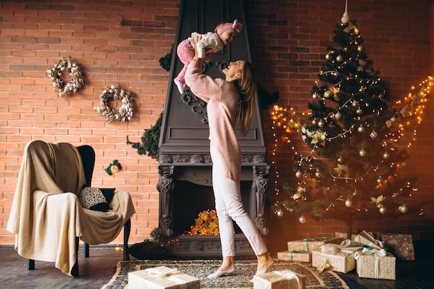 Mère avec fille près de la cheminée à noël