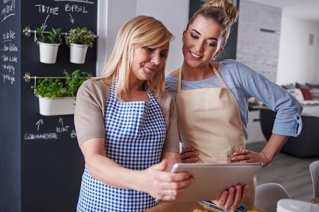 Mère et fille regardant la recette sur une tablette