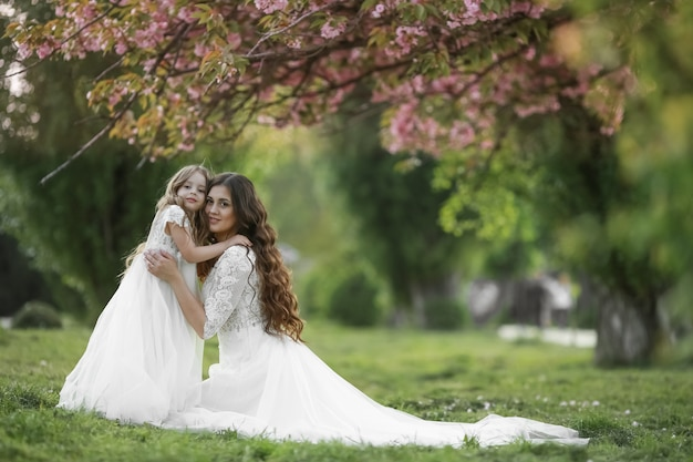 Mère et fille en robe de mariée marchant sur l'herbe verte en robes de mariée blanches