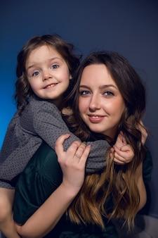 Mère et fille en robes assis sur un lit dans une chambre avec un mur bleu