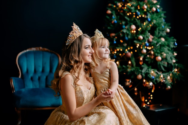 Mère et fille en robes luxueuses près de l'arbre de noël, studio