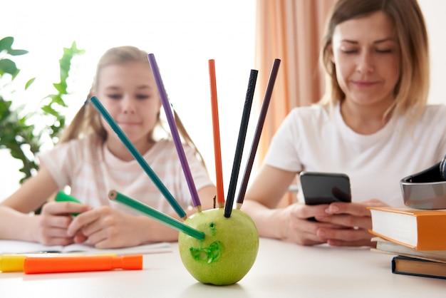 Mère et fille s'amusant pendant l'apprentissage à distance à la maison
