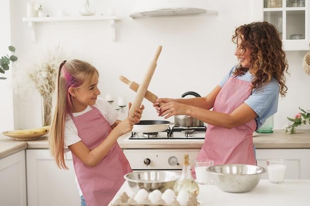 Mère et fille s'amusant avec des rouleaux à pâtisserie dans la cuisine pendant la cuisson