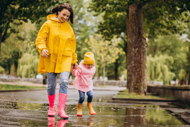Mère avec fille s'amusant à sauter dans les flaques d'eau