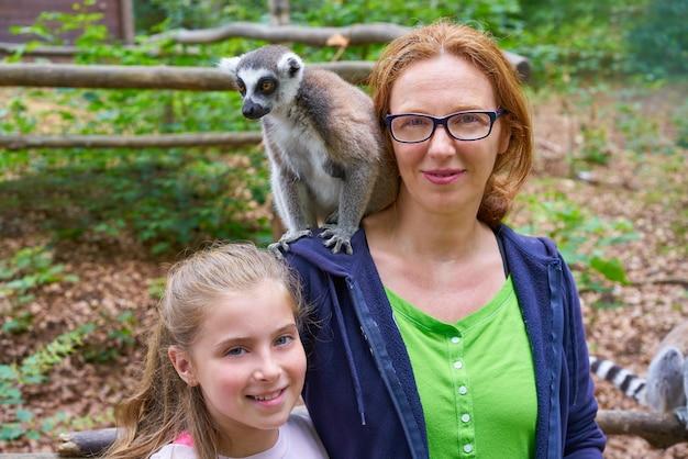 Mère et fille s'amuser avec un lémurien à queue d'anneau