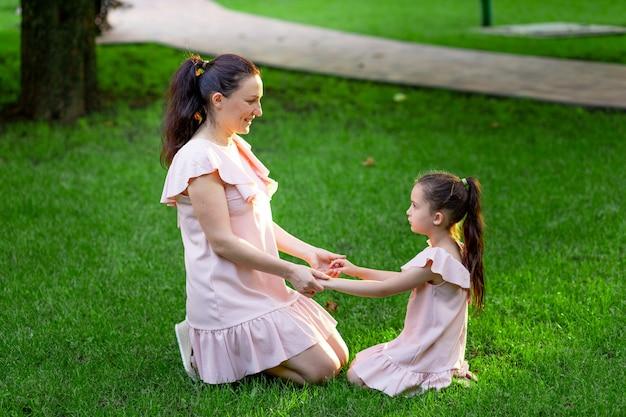 Mère et fille s'asseoir dans le parc sur l'herbe et se tenir la main en été, une conversation entre mère et fille