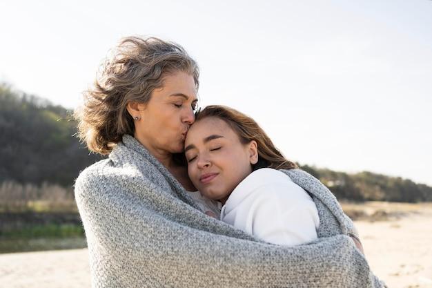 Mère et fille s'embrassant dehors à la plage