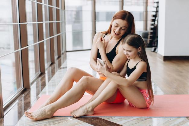 Mère et fille se détendre après l'entraînement assis sur un tapis, en utilisant le téléphone dans la salle de gym pour regarder la vidéo comment faire de l'exercice