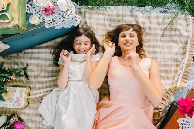 Mère et fille se détendre dans la nature sur un pique-nique