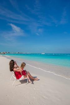 Mère et fille se détendre à la plage tropicale