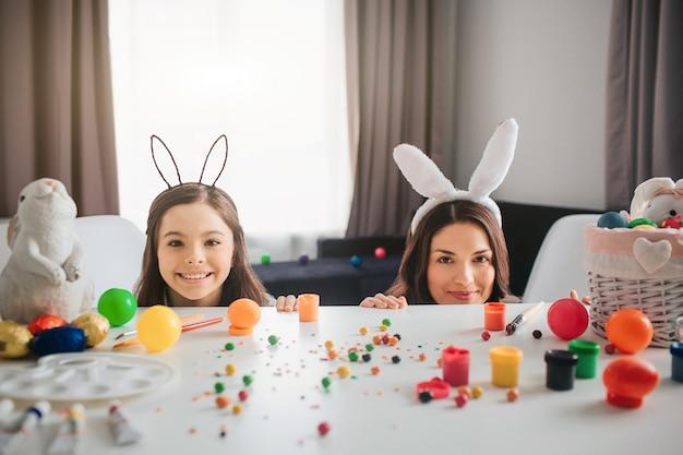 Mère et fille se préparent pour pâques. ils se cachent derrière une table avec des décorations, des œufs et des peintures dessus. mère et fille regardent droit et sourient. ils portent des oreilles de lapin.