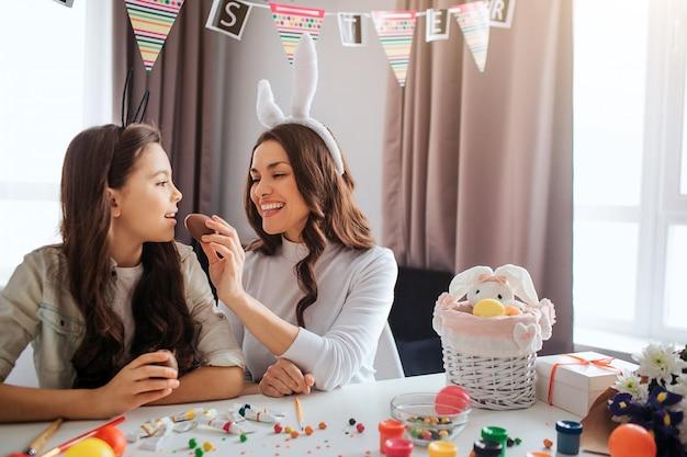 Mère et fille se préparent pour pâques. ils sont assis à table dans la chambre. jeune femme nourrit fille avec oeuf au chocolat. kid garder la bouche ouverte. décoration et peinture avec des bonbons sur table.