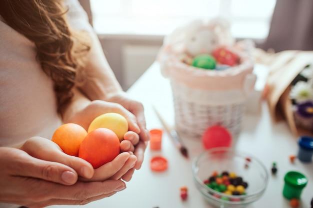 Mère et fille se préparent pour pâques. ils tiennent des œufs colorés ensemble dans les mains. décoration sur table. vue en coupe.