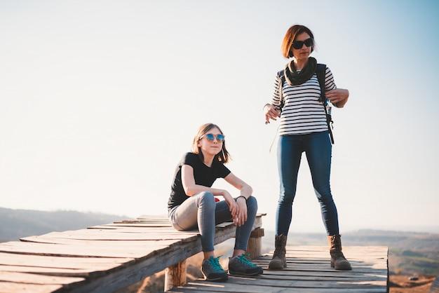 Mère et fille se reposant sur une terrasse en bois