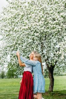 Mère et fille se tiennent dans les bras sous les arbres en fleurs au printemps ou en été, jupe rouge, robes légères