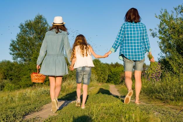 Mère et fille se tiennent la main, marchent le long de la route de campagne.